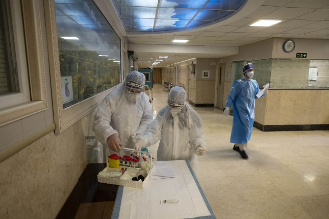 Iranian medical personnel wearing protective gear check coronavirus test samples as they work at a quarantine section of the Rassolakram hospital in western Tehran on March 11. Photo by Morteza Nikoubazl/UPI