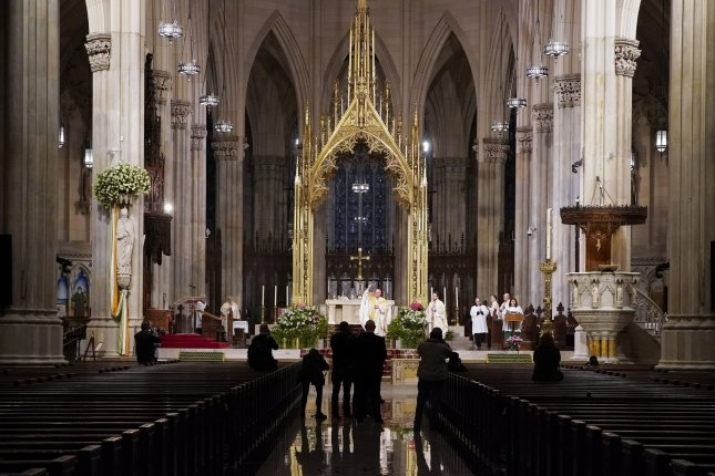 Church pews are empty of parishioners due to the Coronavirus pandemic while photographers take photos of Cardinal Timothy Dolan who offers Easter Sunday Mass at St. Patrick's Cathedral in New York City. Photo by John Angelillo/UPI