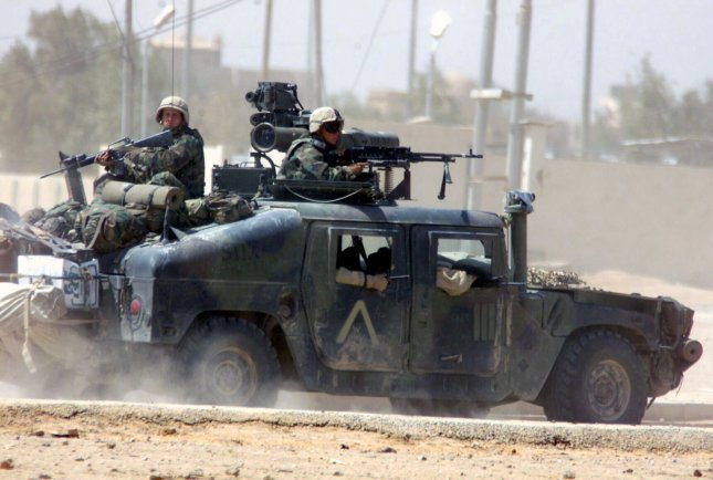 U.S. Marines, manning machine guns, ride a High Mobility Multipurpose Vehicle (Humvee) toward Nasiriyah, Iraq, April 1, 2003, to support troops in a firefight. The U.S.-led invasion of Iraq had begun two weeks earlier, on March 19, 2003. File Photo/UPI