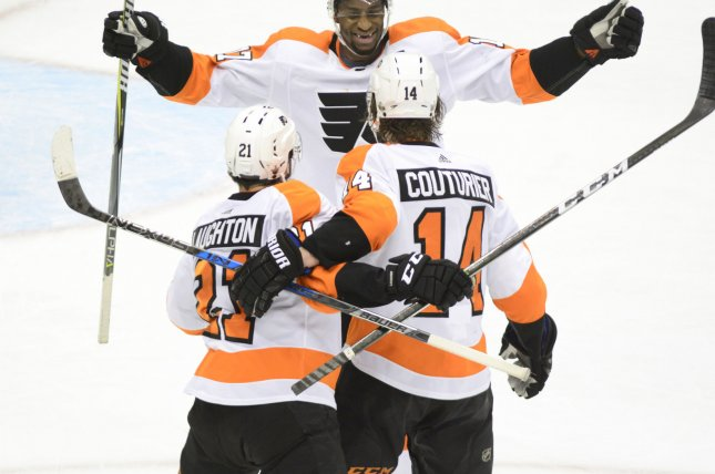 Philadelphia Flyers right wing Wayne Simmonds (17) joins center Sean Couturier (14) and center Scott Laughton (21) to celebrate the game winning goal against Pittsburgh Penguins on April 20 at PPG Paints Arena in Pittsburgh. Photo by Archie Carpenter/UPI
