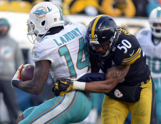 Miami Dolphins receiver Jarvis Landry attempts to break free from the grasp of Pittsburgh Steelers linebacker Ryan Shazier during the 2017 playoffs. Photo by Archie Carpenter/UPI
