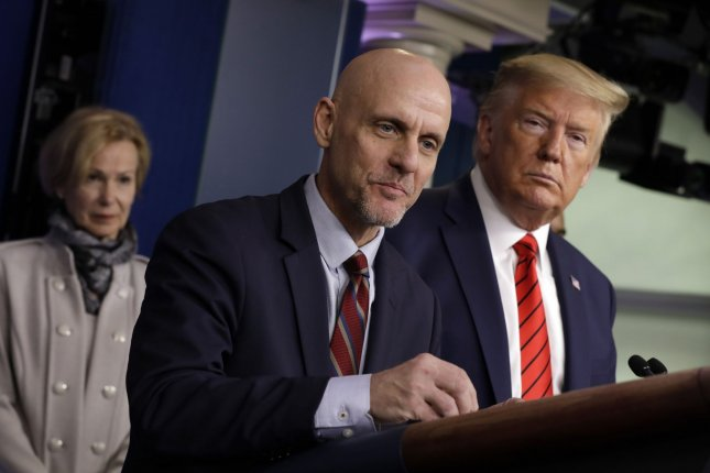 FDA Commissioner Stephen Hahn speaks to reporters while standing next to President Donald Trump during a news briefing at the White House on March 19. Trump said he may overrule stricter FDA guidance on evaluating a COVID-19 vaccine. File Photo by Yuri Gripas/UPI