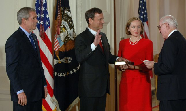 Judge John Roberts (2nd L) is sworn in by Supreme Court Justice John Paul Stevens (R) as his wife, Jane Roberts, holds the Bible and U.S. President George W. Bush watches on September 29, 2005, in the East Room of the White House. File Photo by Roger L. Wollenberg/UPI