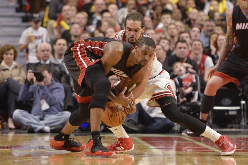 Former Chicago Bulls center Joakim Noah (R) steals the ball from Miami Heat center Chris Bosh. UPI/Brian Kersey