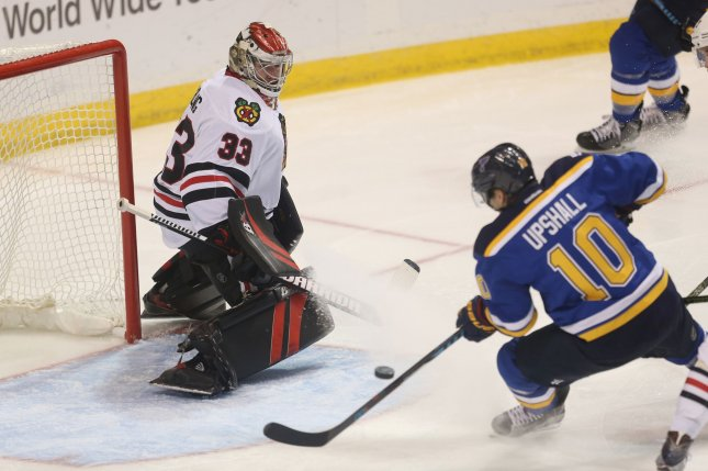 St. Louis Blues' Scottie Upshall tries to shoot the puck off balance as former Chicago Blackhawks goaltender Scott Darling defends in the third period at the Scottrade Center in St. Louis on December 17, 2016. File photo by Bill Greenblatt/UPI