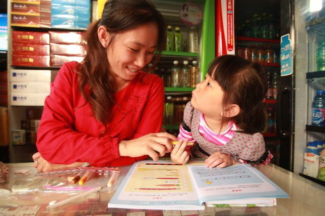 A mother helps her daughter with homework while at work in Kunming, the capital of China's southern Yunnan Province, on September 26, 2012. Recent test scores show that China leads the United States in reading, math and science. UPI/Stephen Shaver