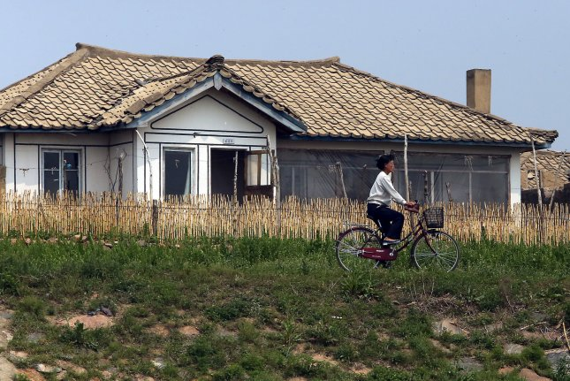A North Korean woman rides a bike on the banks of the Yalu River near Sinuiju, across the Yalu River from Dandong, China's largest border city with North Korea. North Korea has improved hospital services since 2008, leading to a decline in mortality rates, according to a new U.N. report. Photo by Stephen Shaver