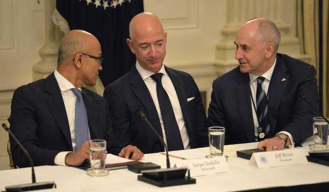 (L-R) Microsoft CEO Satya Nadella, Amazon CEO Jeff Bezos and White House Advisor Christopher Liddell chat as they await the arrival of President Donald Trump at the White House, June 19. This year, Bezos was named the richest man in the world with a net worth of more than $90 billion. File Photo by Mike Theiler/UPI