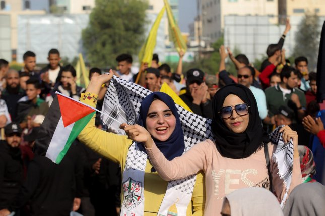 Supporters of exiled Palestinian politician and Fatah former security chief Mohammed Dahlan wave the group's yellow flag during a commemoration ceremony held on the 14th anniversary of Yasser Arafat's death Tuesday in Gaza City. Photo by Ismael Mohamad/UPI