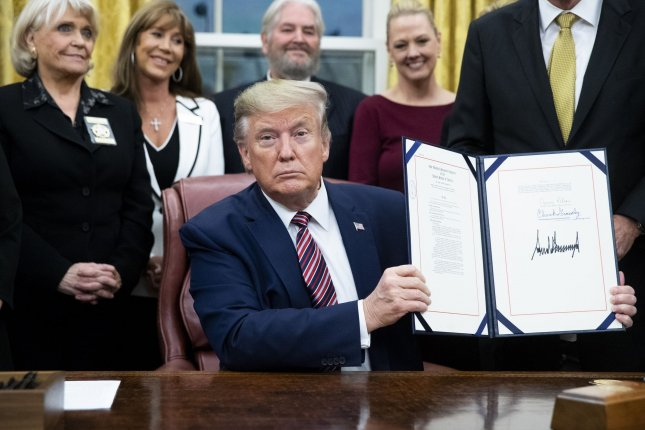 U.S. President Donald Trump holds up H.R. 724, the Preventing Animal Cruelty and Torture Act, after signing it during a ceremony in the Oval Office of the White House in Washington, D.C., on Monday. Photo by Michael Reynolds/UPI