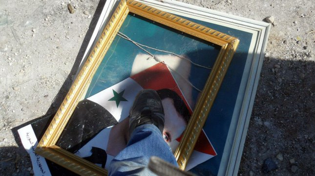 A member of the Free Syrian Army steps on a picture of Syrian President Bashar al-Assad one day after the Syrian defense minister was killed in an attack in Damascus. in ,Aleppo in Syria, July 19, 2012 . UPI/Khaled Tallawy
