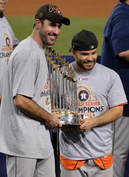 Houston Astros' Jose Altuve holds Commissioners Trophy with pitcher Justin Verlander, left, after defeating the Los Angeles Dodgers in the 2017 MLB World Series . The Astros beat the Dodgers 5-1 to claim their first ever World Series championship. Photo by Jim Ruymen/UPI
