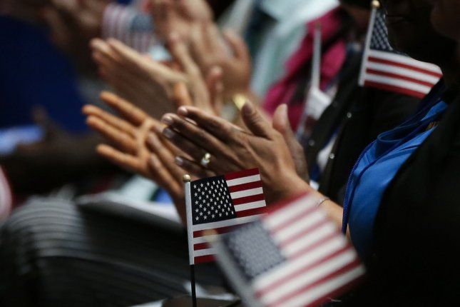 New citizens of the United States applaud with American Flags as U.S. Citizenship and Immigration Services administer the Oath of Allegiance to naturalized citizens during a ceremony in New York City on July 3, 2018. Photo by John Angelillo/UPI
