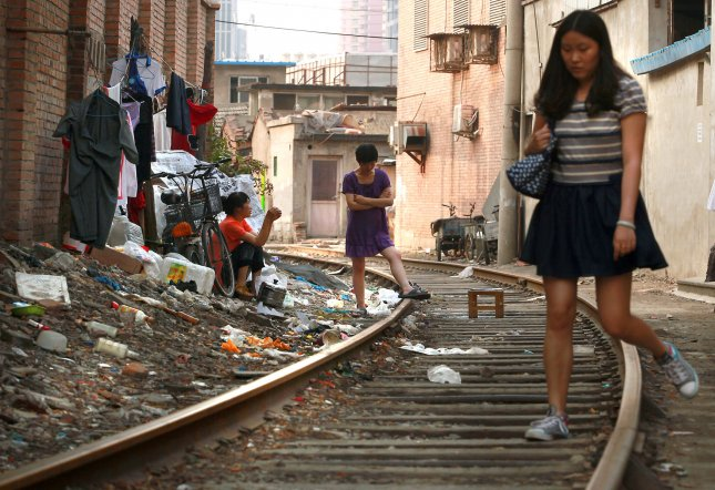 Chinese women sit outside their low-income apartment next to train tracks in Beijing. Photo by Stephen Shaver/UPI