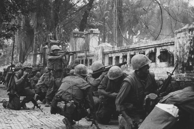The scene is Hue, during its darkest moment-the infamous TET offensive. U.S. marines are keeping low because of intense sniper fire from communists units which seized two-thirds of the ancient imperial Capital 2/4/1968. The Marines were pinned down behind this wall near the old citadel and radioed for support. U.S. spokesmen reported that leathernecks hauled down the North Vietnamese flag after seven days of fighting and recaptured the city. (UPI photo)