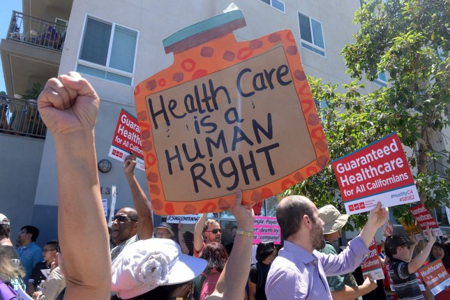 A protester holds a sign supporting universal health coverage at a rally in California. A new survey Friday showed that public sentiment toward Republican healthcare reform is turning more unfavorable. File Photo by Jim Ruymen/UPI