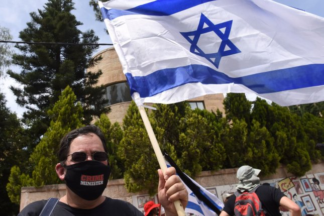 A man holds the Israeli national flag, during a protest against Prime Minister Benjamin Netanyahu's right to form a government since he is facing a criminal trial. Photo by Debbie Hill/UPI