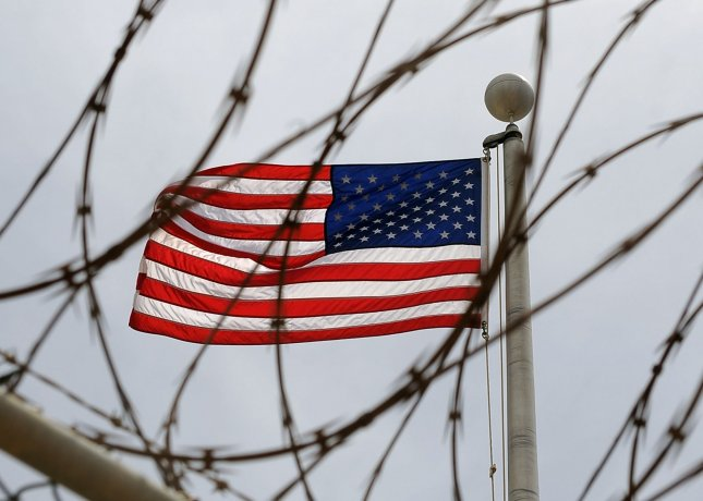 An American Flag is seen through razor wire at Camp VI in Camp Delta where detainees are housed at Naval Station Guantanamo Bay in Cuba. UPI/Roger L. Wollenberg