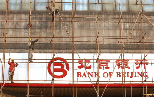 Chinese workers erect scaffolding around a Bank of Beijing branch in Beijing on November 12, 2010. China's trade surplus grew in October as both exports and imports rose on-year, China's government said this week, adding to pressure on Beijing during the G20 summit to let its currency appreciate. UPI/Stephen Shaver