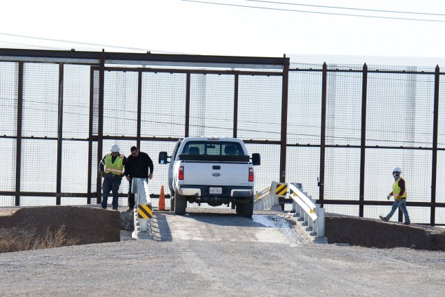 Border Patrol agents stand near a gate in the border fence that connects the rural farming community of Socorro, Texas, just outside El Paso, to Juarez, Mexico on February 12. File Photo by Natalie Krebs/UPI