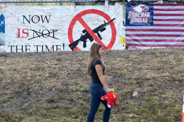 A student holding her bear walked past signs after being dismissed from class at Marjory Stoneman Douglas High School in Parkland, Fla., on February 28, the first day back. The school was closed for two weeks after the school shooting that killed 17 students and teachers. Photo by Gary Rothstein/UPI