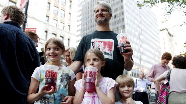 Jim Sara, Alana and Benjamin Lesczynski hold large drinks at the Million Big Gulp March protest organized by the group NYC Liberty, City Council members and other demonstrators to express opposition to Mayor Michael R. Bloomberg's proposal to prohibit licensed food service establishments from using containers larger than 16 ounces to serve high-calorie drinks at City Hall Park in New York City on July 9, 2012. The proposed first-in-the-nation ban would impose a 16-ounce limit on the size of sweetened drinks sold at restaurants, movie theaters, sports venues and street carts. It would apply to bottled drinks as well as fountain sodas. UPI/John Angelillo