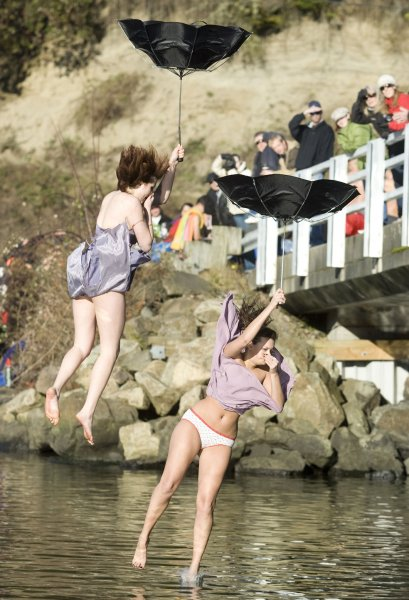Two participants wear prom dresses and hold umbrellas in the 27th annual Polar Bear jump into the Burley Lagoon in Olalla, Washington on January 1, 2011. Over 300 hardy participants braved the chilly lagoon waters to join in on the annual New Year's Day Tradition. UPI/Jim Bryant