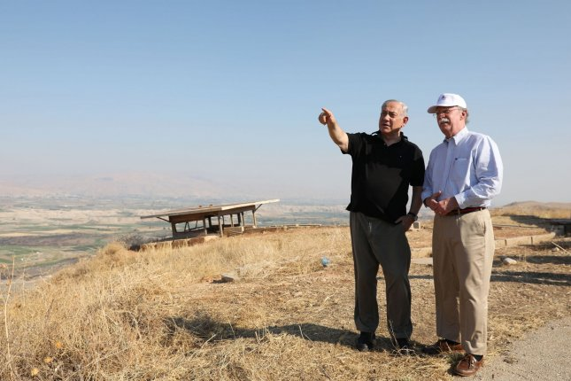 Former U.S. national security adviser John Bolton (R) and Israeli Prime Minister Benjamin Netanyahu visit an old army outpost overlooking the Jordan Valley,  between the Israeli city of Beit Shean and the Palestinian city of Jericho, West Bank, on June 23. File Photo by Abir Sultan/UPI