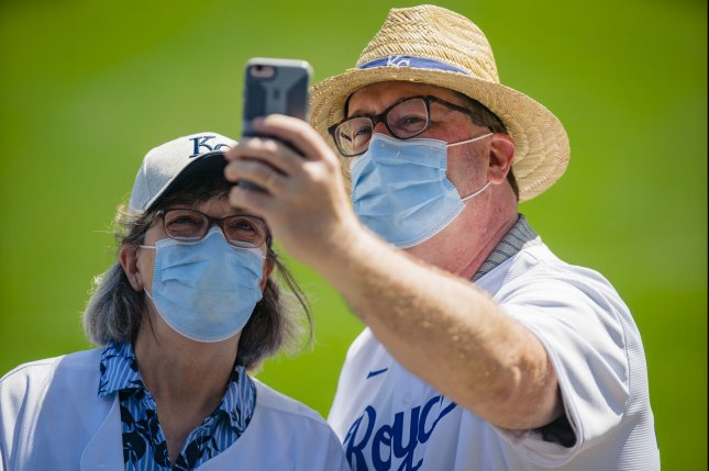 Kansas City Royals fans take a selfie with their masks on before the Royals take on the Texas Rangers at Kaufman Stadium in Kansas City, Mo., on April 04. The CDC said it expects COVID-19 cases, deaths and hospitalizations to drop sharply in July. File Photo by Kyle Rivas/UPI