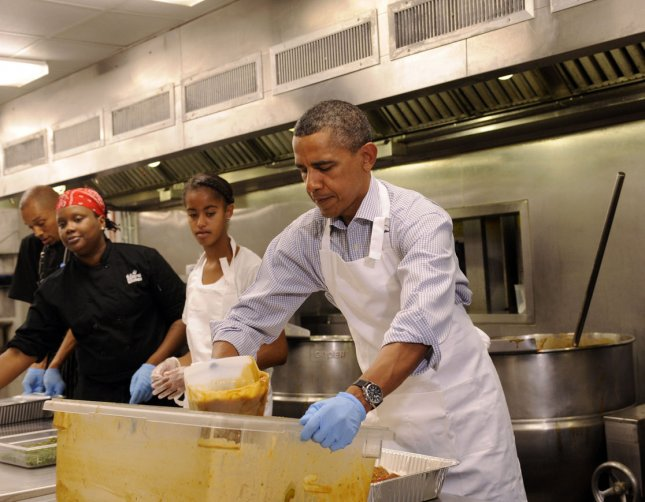 U.S. President Barack Obama with daughter Malia Obama, and, from left, Jeffrey Ragsdale and Jamillah Linkins, participate in a service project at DC Central Kitchen, on September 10, 2011, in Washington, DC. UPI/Leslie E. Kossoff/POOL