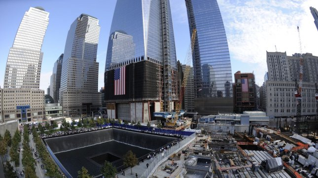 Families visit the North Memorial Pool, with One World Trade Center under construction in rear, during tenth anniversary ceremonies at the site of the World Trade Center September 11, 2011, in New York. UPI/Robert Deutsch/Pool