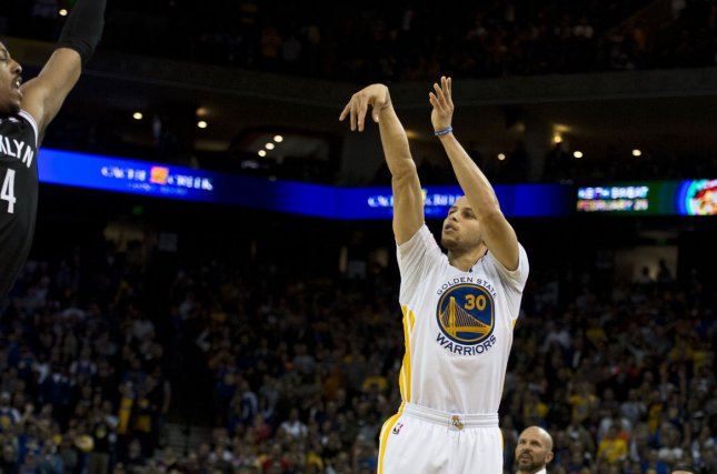 Golden State Warriors Stephen Curry (30) launches a three point coffin nail into the Brooklyn Nets in the final minute as Nets Head Coach Jason Kidd watches at Oracle Arena in Oakland, California on February 22, 2014. The Warriors defeated the Nets 93-86. UPI/Terry Schmitt