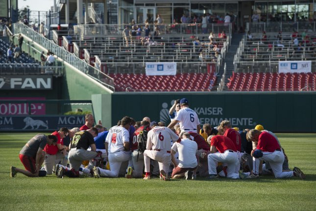 The Republican congressional baseball team bow their heads while gathering prior to their charity game against the Democrats at Nationals Park in Washington, D.C., on Thursday evening. The Republican team was practicing Wednesday before a gunman opened fire and injured five. Photo by Molly Riley/UPI