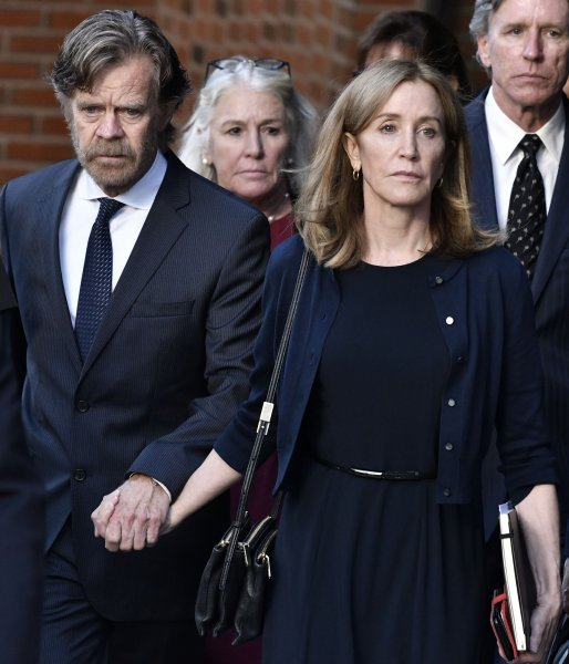 Felicity Huffman (R) leaves her sentencing hearing with husband William H. Macy on Sept. 13. at the John Joseph Moakley United States Courthouse in Boston. File Photo by Josh Reynolds/UPI