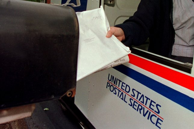 A bundle of mail being placed in a residential mailbox (File/Bill Greenblatt/UPI)