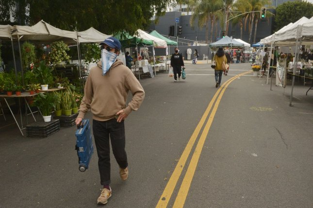 Shoppers at the Hollywood farmer's market comply with Mayor Eric Garcetti's orders to the extent that they can in Los Angeles on Sunday. Photo by Jim Ruymen/UPI