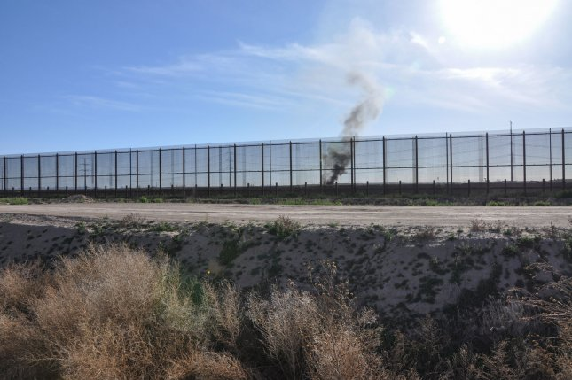 Smoke is visible across the U.S.-Mexico border in Juarez, Mexico, through the border fence that connects the farming community of Socorro, Texas, just outside of El Paso, to Juarez, Mexico on February 12, 2019. File Photo by Natalie Krebs/UPI