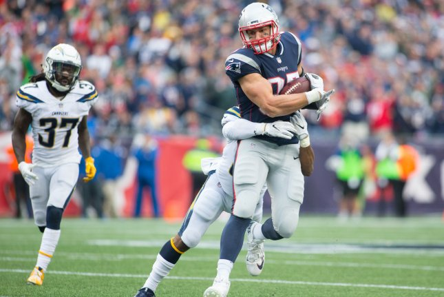 New England Patriots tight end Rob Gronkowski (87) drags Los Angeles Chargers safety Adrian Phillips (31) behind him on a 26-yard reception in the fourth quarter at Gillette Stadium in Foxborough, Mass. Photo by Matthew Healey/UPI