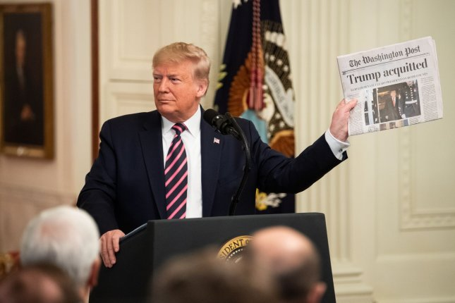 President Donald Trump holds a copy of the Washington Post featuring a headline on his impeachment acquittal saying This is what the end result is. Photo by Kevin Dietsch/UPI