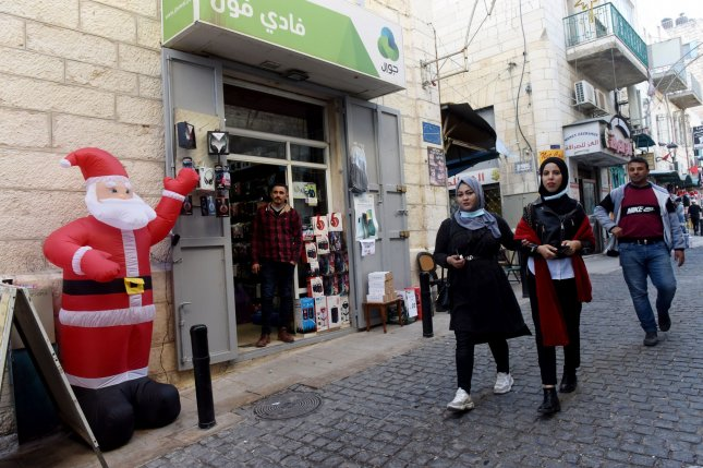 Palestinians walk past a Santa Claus decoration inBethlehem, West Bank, on Thursday. Bethlehem Mayor Anton Salman said the biblical town is suffering economically since tourism is its main source of income, particularly this time of year. Photo by Debbie Hill/UPI