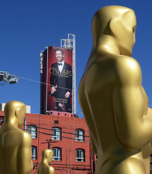 A poster of show host Jimmy Kimmel looms over Oscar statues awaiting their placement on the red carpet as preparations are underway for the 89th annual Academy Awards on February 23. Kimmel is to host the Oscars in 2018, as well. File Photo by Jim Ruymen/UPI