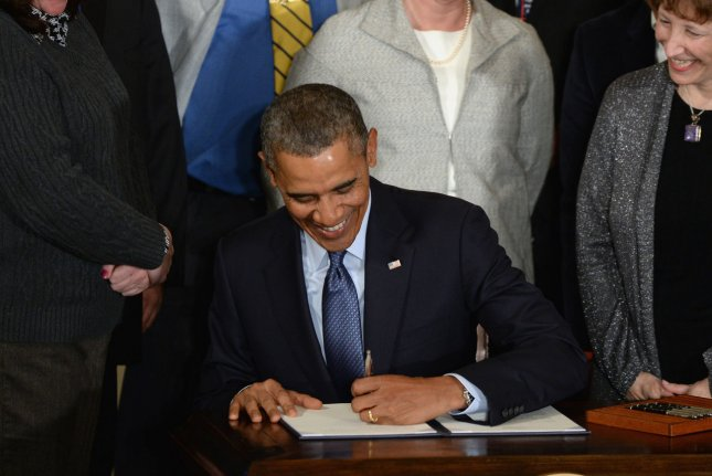 U.S. President Barack Obama smiles as he laughs with guests as he signs a presidential memorandum increasing overtime protections for workers during an event in the East Room of the White House in Washington, DC on March 13, 2014. The White House stated that the president would veto the Enforce the Law legislation the house passed last night to make it easier for congress to sue the president. UPI/Pat Benic