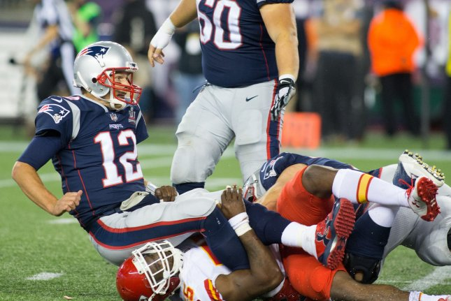 New England Patriots quarterback Tom Brady (12) is dragged down by Kansas City Chiefs linebacker Dee Ford (55) after a pass in the fourth quarter on September 7 at Gillette Stadium in Foxborough, Mass. Photo by Matthew Healey/ UPI