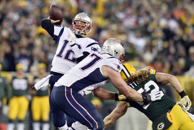 New England Patriots quarterback Tom Brady (12) throws a pass as former Patriots tackle Nate Solder (77) blocks Green Bay Packers outside linebacker Clay Matthews (52) during the fourth quarter on November 30, 2014 at Lambeau Field in Green Bay, Wisconsin. File photo by Brian Kersey/UPI