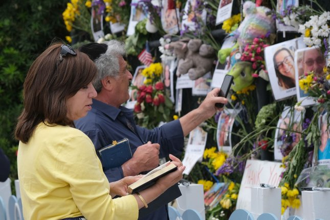 Jack Franco and his wife stop to say a prayer for the missing people at the memorial outside St. Joseph Catholic Church near the collapsed Champlain Towers South condo in Surfside, Fla. on July 7. Officials said Tuesday the death toll has now reached 95 victims. Photo by Gary I. Rothstein/UPI