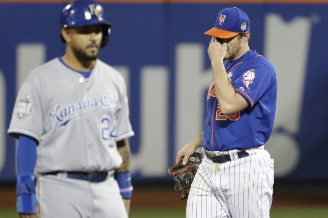 Kansas City Royals Christian Colon stands on 2nd base while New York Mets Daniel Murphy reacts after making an error in the 12th inning in game 5 of the World Series at Citi Field in New York City on November 1, 2015. Photo by John Angelillo/UPI
