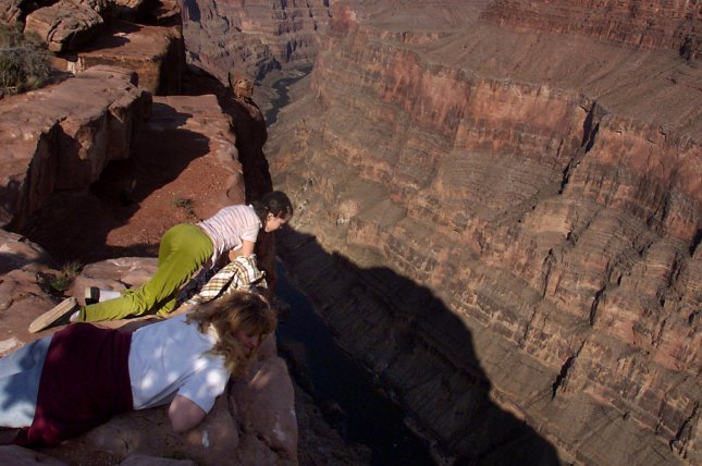 A child crawls to the rim to peer down at the Colorado River at Tuweep in the Grand Canyon National Park. File Photo by Terry Schmitt/UPI