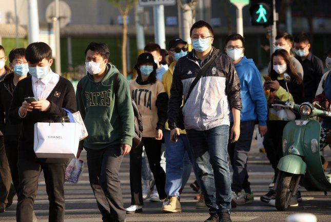 Pedestrians in Beijing, China, continue to wear face masks on Tuesday although the government has declared the coronavirus threat has largely passed. Photo by Stephen Shaver/UPI