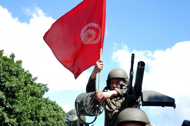 A Tunisian soldier hold Tunisia flag, as Islamists protest against the Tunisian government demanding for the wearing of the veil for all Tunisian women on April 2, 2011 in Tunis. UPI\Hichem Borni