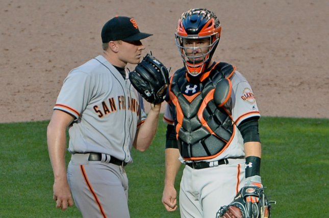 San Francisco Giants relief pitcher Mark Melancon (L) talks with catcher Buster Posey in the ninth inning. File photo by Art Foxall/UPI